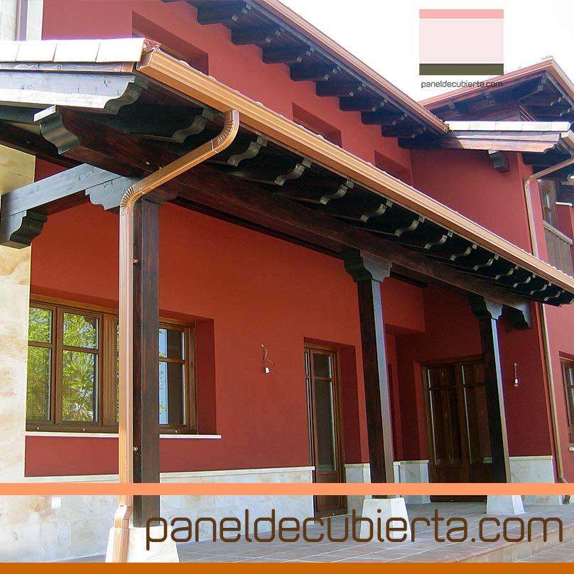 Porche realizado con panel de cubierta acabado decorativo en maderas nobles.